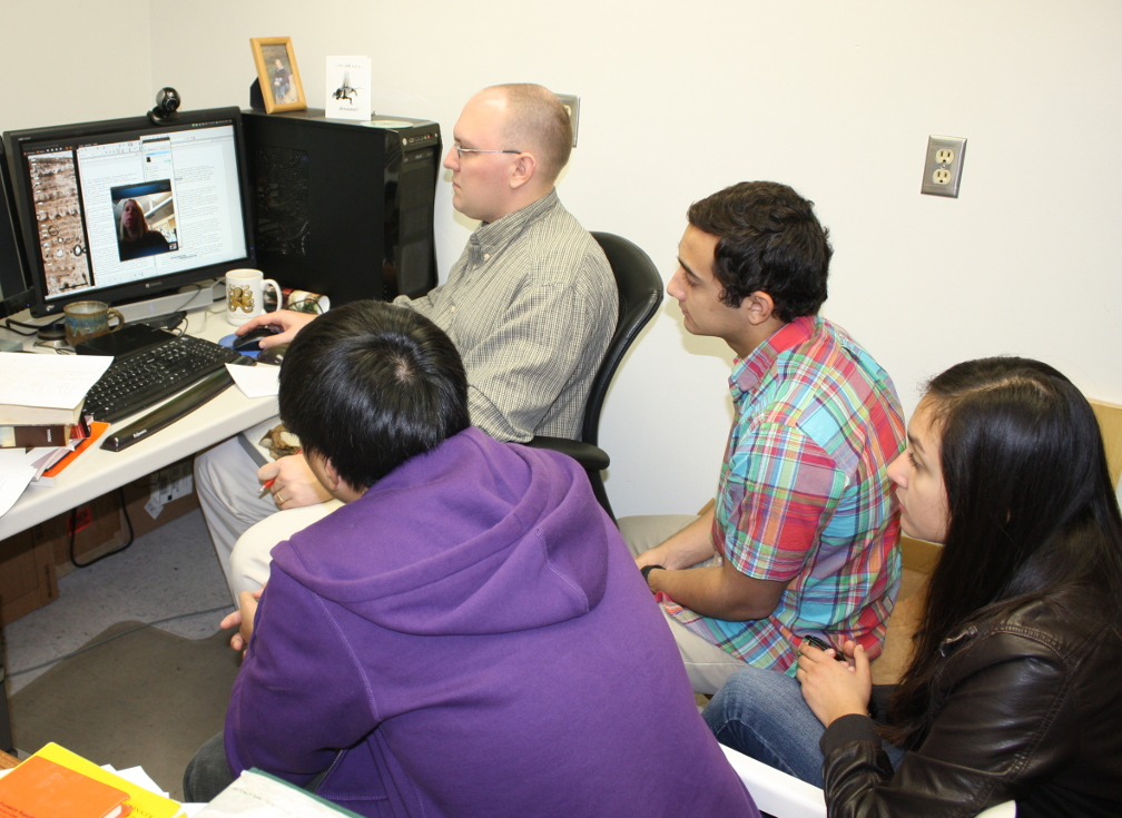 "On location at the Alf Museum, (from left) Derek Chok, Andy Farke, Brandon Scolieri, and Annisa Herrero talk about the bone structure of ""Joe"" via a teleconference with Sarah Werning (visible on the computer screen)."